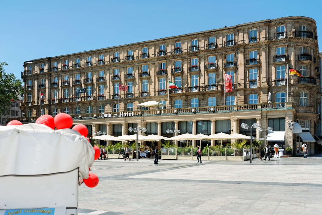 Dom Hotel zu Köln mit Brautpaar-Rikscha.